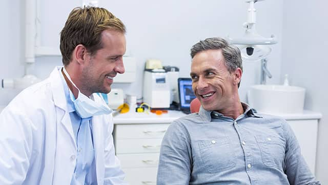 dentist and patient interacting with each other and smiling