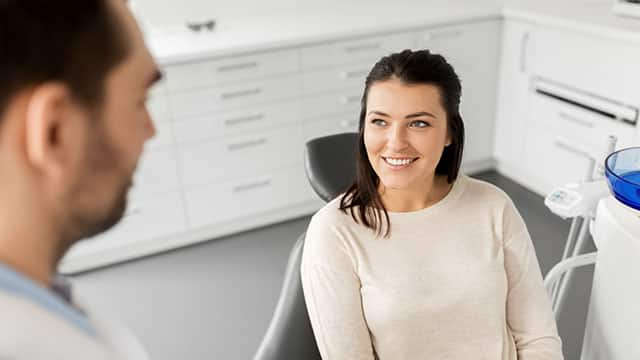 A smiling female patient talking to a dentist at dental office