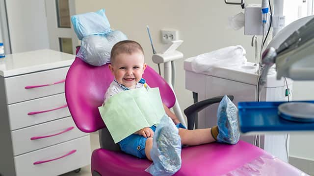 baby smiling while sitting in a dental chair