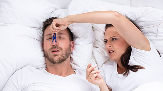 A woman Trying To Stop Man's Snoring With Clothespin