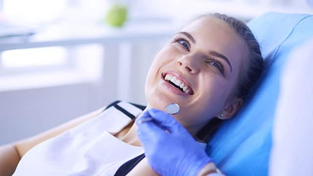 woman having her teeth examined by a dentist