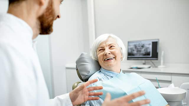 An elder woman sitting  and smiling during the consultation with dentist at the dental office