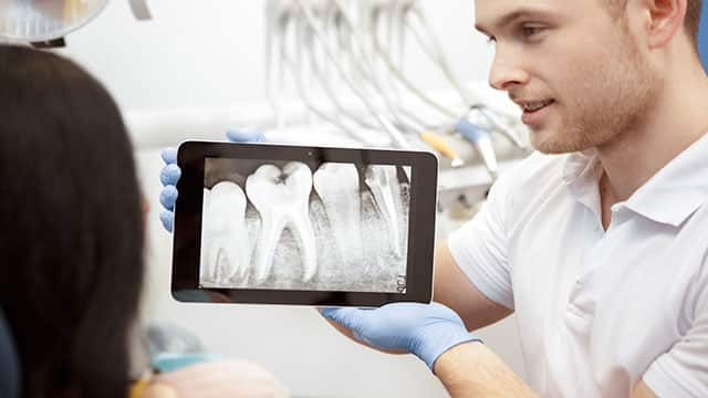 dentist showing his patient an x-ray of teeth on a  digital tablet