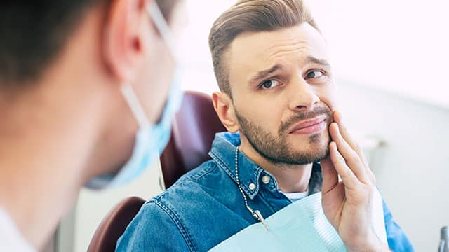 A man with a worried face is holding his hand on his cheek because of irritating pain in front of a dentist