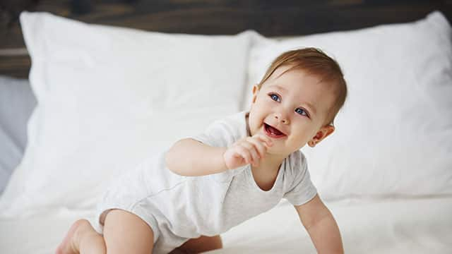 Happy baby crawling on the bed