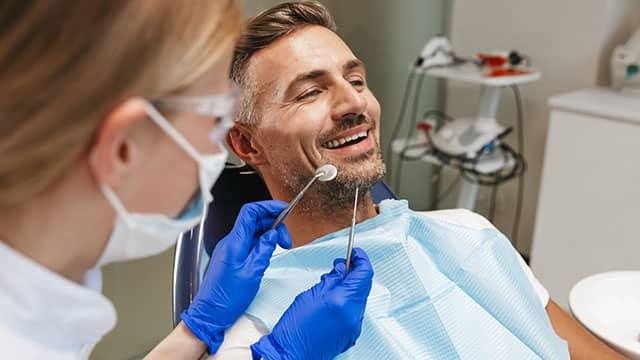 Happy young man sitting in dental chair ready for treatment