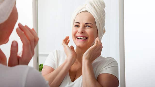 Smiling  woman looking at a mirror in a bathroom with hands near her jaw