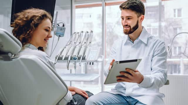 A male dentist discussing results with a female patient using a tablet in a dental office