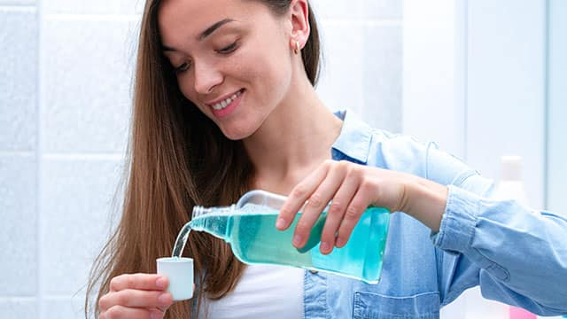 A young woman pouring mouthwash from bottle into cap in the bathroom