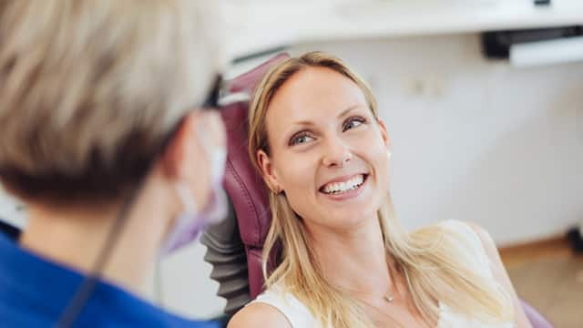 Female dentist talks with a smiling female patient