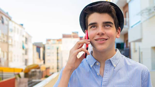 Young man wearing braces and holding a mobile phone to his ear on the city street