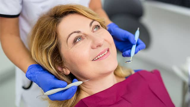 An older woman is at the dentist receiving a dental procedure