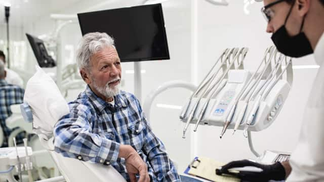 An senior man in a flannel shirt talking with his dentist