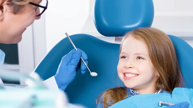 Smiling little girl about to be examined by a dentist