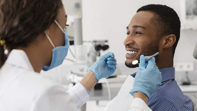 Young  guy smiling to his female dentist