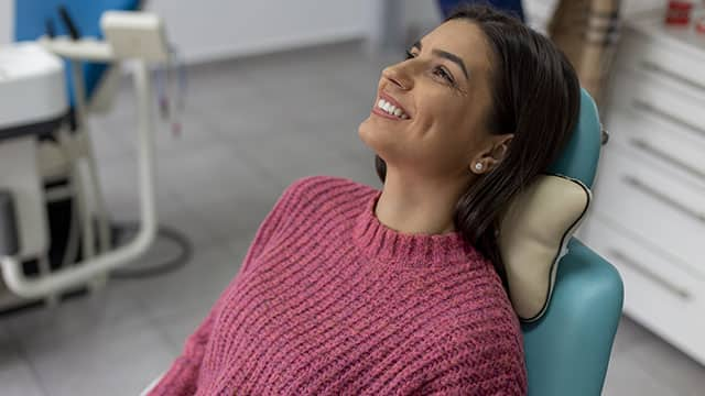 A young woman smiling while sitting on the dentist's chair and waiting for her teeth treatment