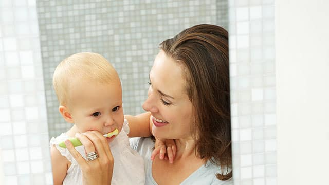 Mother teaching her baby how to brush teeth