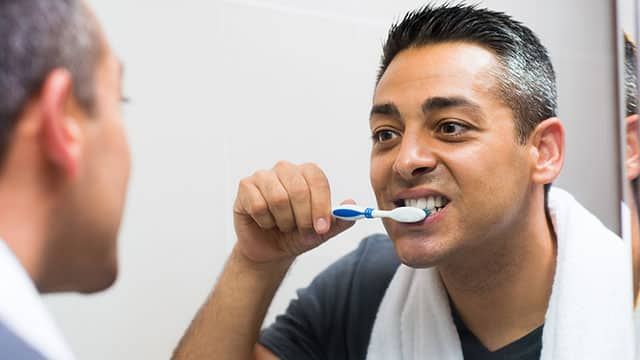 A man brushing his teeth in front of the mirror