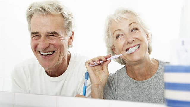 Happy couple brushing their teeth and laughing