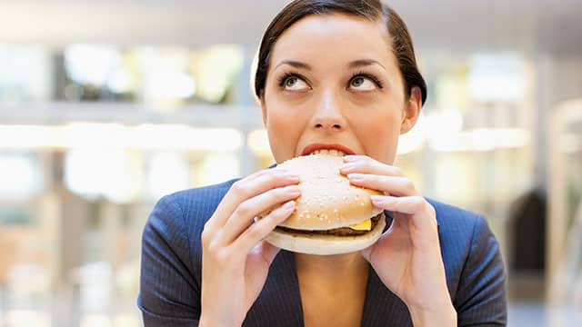 Young woman is eating a hamburger