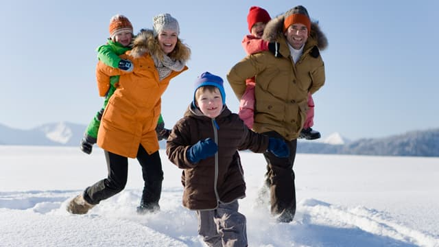 A family of five in cold weather clothes walking in the snow