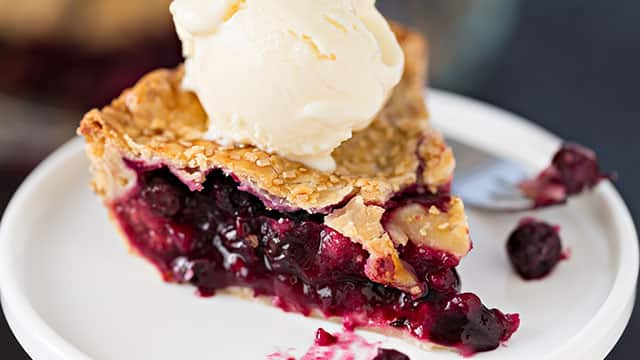A sweet berry pie and ice cream on a top
