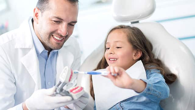 A dentist is showing to a little girl how to brush