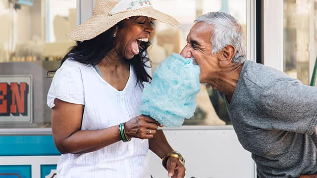 Senior couple laughing and eating cotton candy