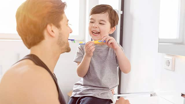 Father and son laughing and brushing their teeth together in the bathroom