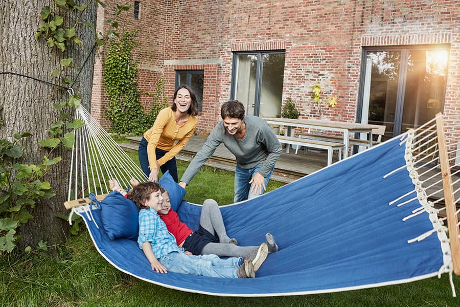 Happy family smiling and playing in a hammock