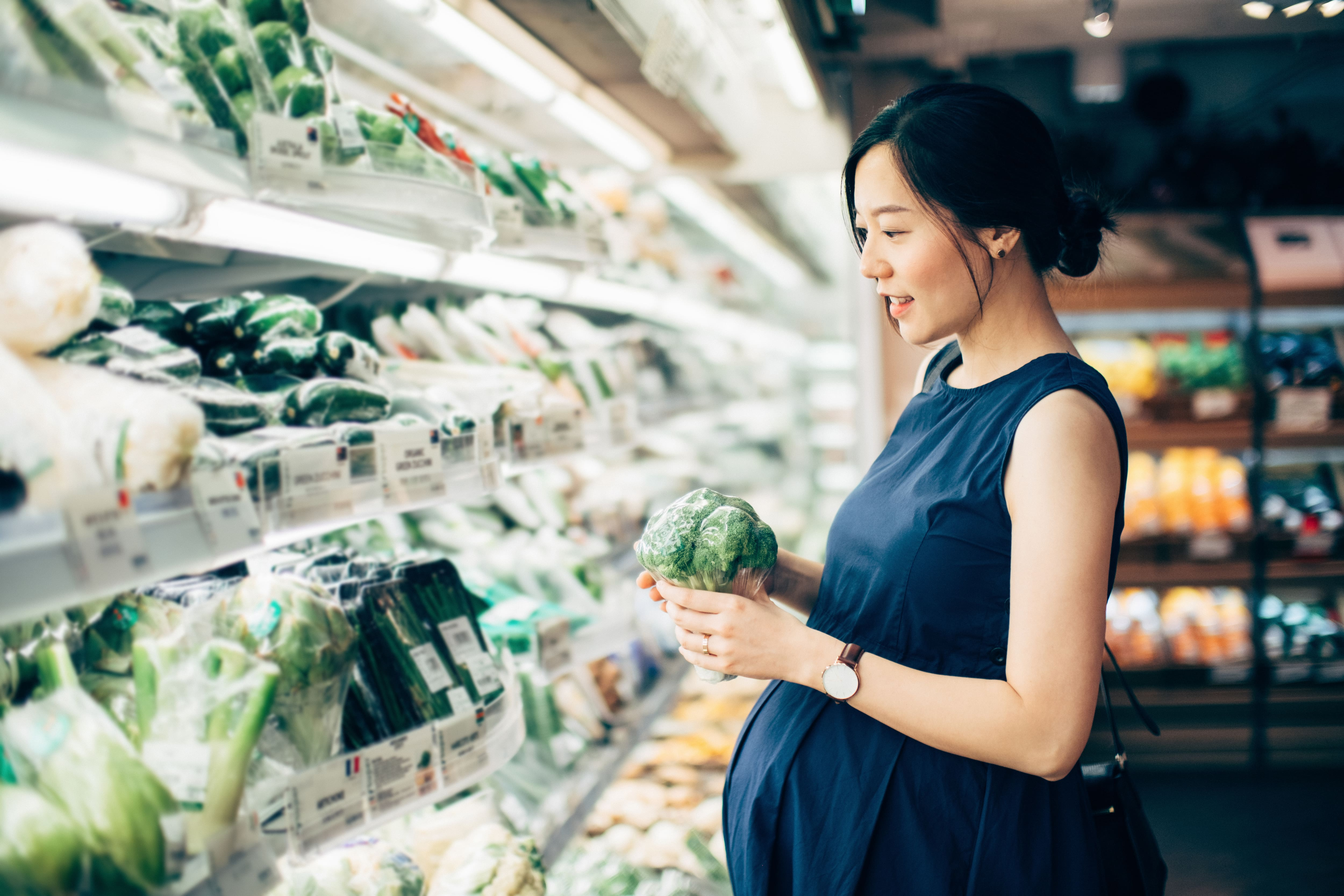 Pregnant woman grocery shopping and looking at the vegetable aisle in a supermarket