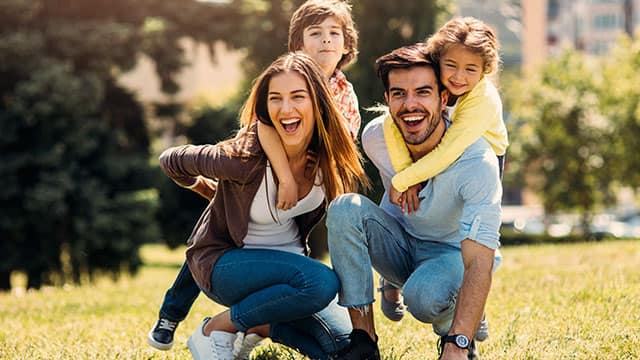 Parents with two kids smiling outdoors