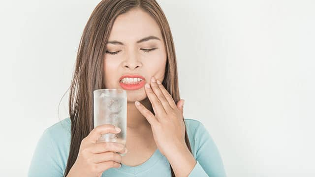 A woman with sensitive teeth drinking ice water