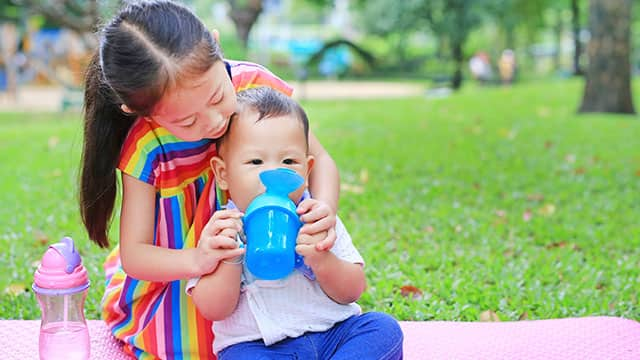 Sister helping her brother use sippy cup