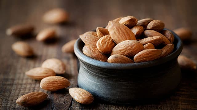 Almonds in black bowl that are good for your teeth