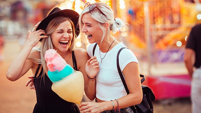 Shot of happy female friends in amusement park eating cotton candy. Two young women enjoying a day at amusement park.