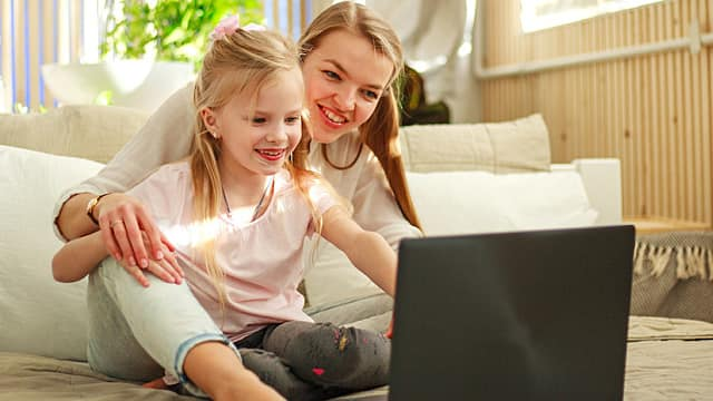 Happy family mother with daughter using computer laptop at home, modern lifestyle