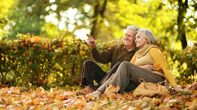 Mature Couple Sits in Park in Autumn