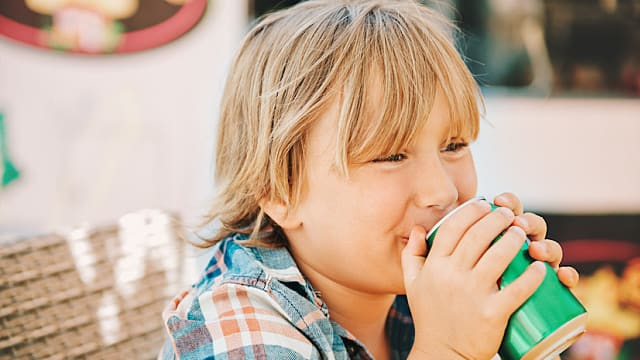 Little kid boy drinking soda in cafe on a very hot day