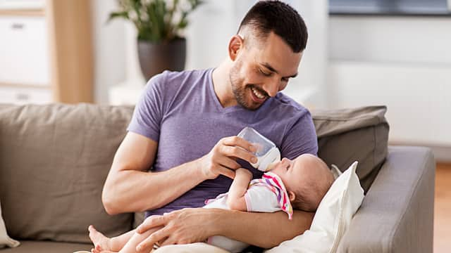father feeding baby daughter from bottle at home