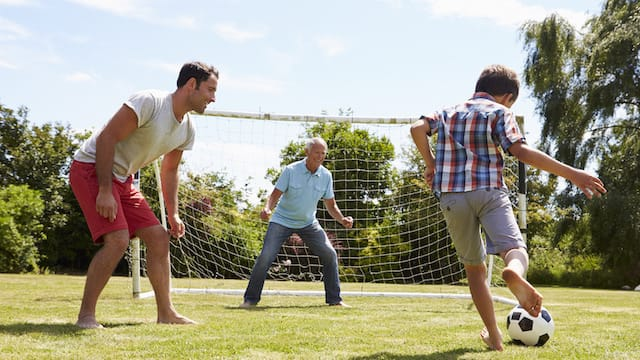 Grandfather, Grandson And Father Playing Football In Garden