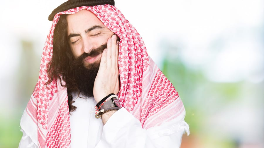 Arabian business man with long hair wearing traditional keffiyeh scarf touching mouth with hand