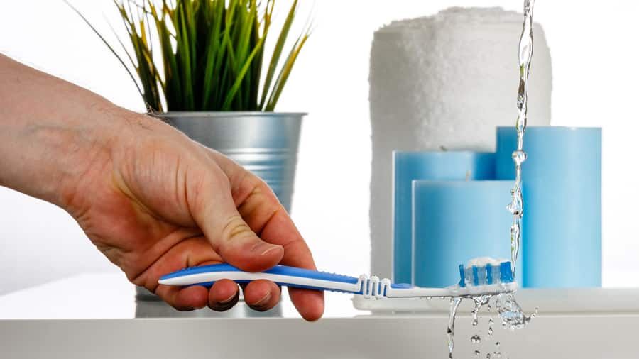 Clean the toothbrush by water