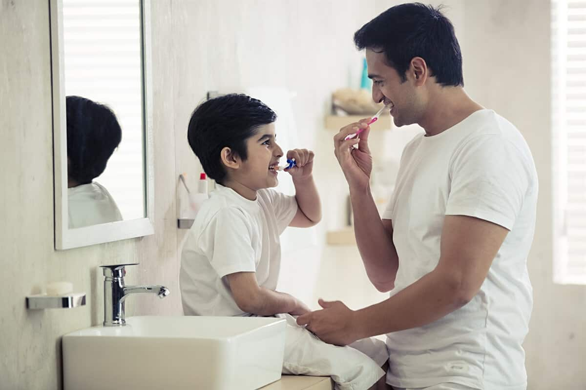 Man brushing his teeth with his son