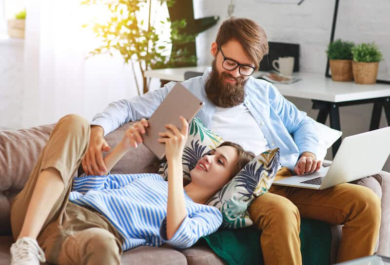 happy couple relaxing at home with laptop and tablet