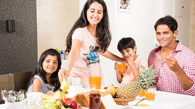 Happy indianasian young family eating healthy breakfast