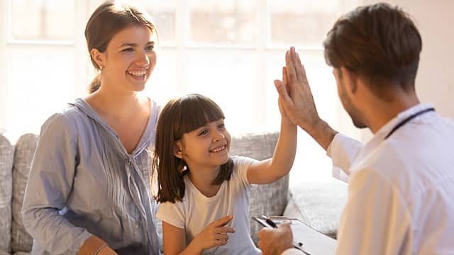 Happy cute child girl giving high five to male pediatrician