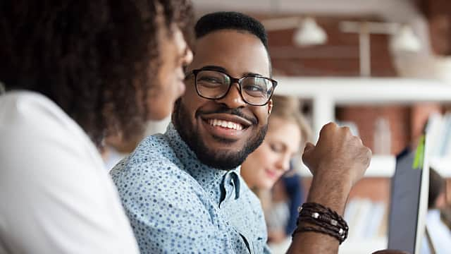 Smiling African American male employee look at colleague chattin