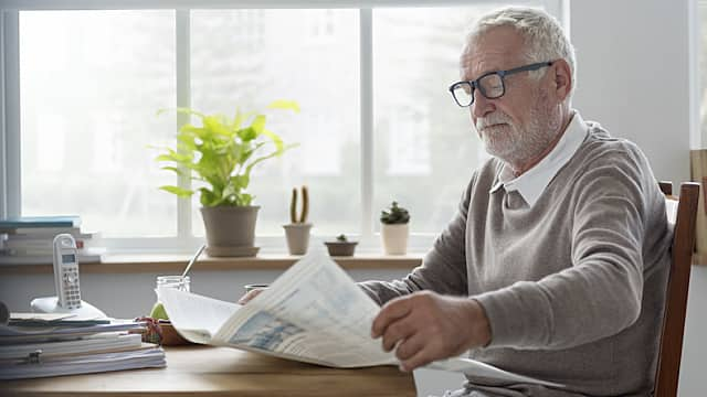 Senior Man Reads Newspaper at Home