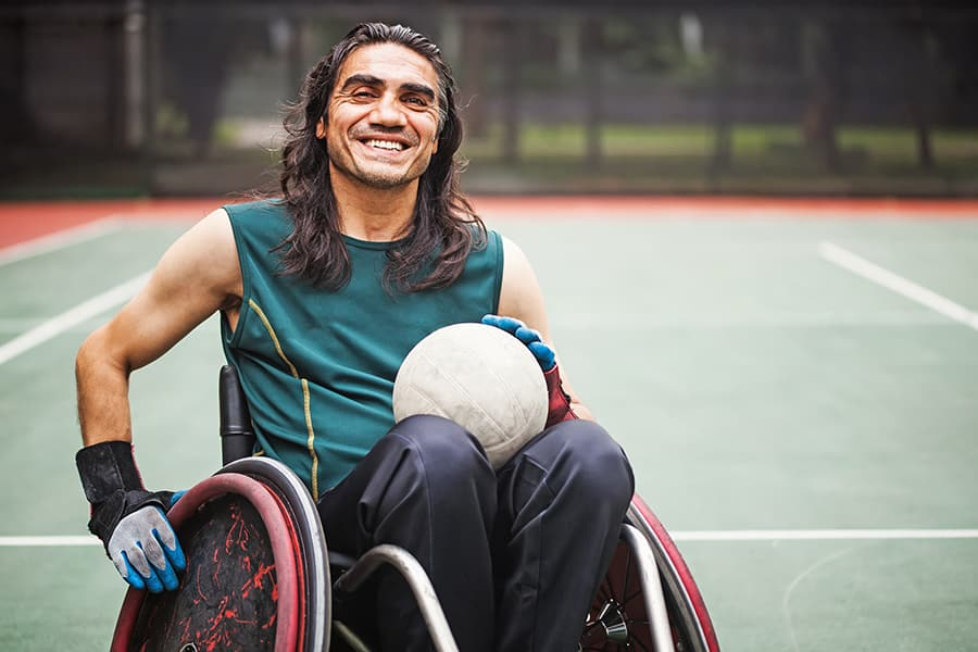 man in wheelchair with a green tank top playing rubgy and smiling